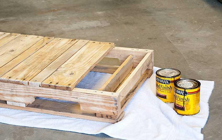 Качели из поддона, шаг 2: обработка деревянного сидения влагозащитным составом и лакирование.